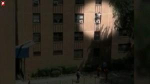 Kind steht auf Klimaanlage des dritten Stockwerkes.