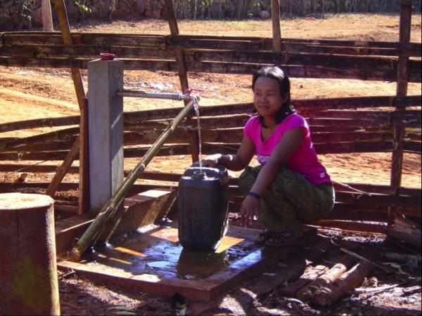 Frau an Brunnen mit Wasserfilter
