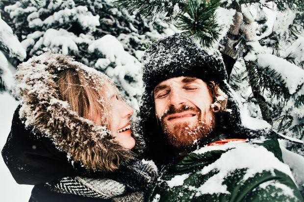 Mann hält eine Frau in einer Schneelandschaft im Arm. Beide sind voll Schnee und lachen.
