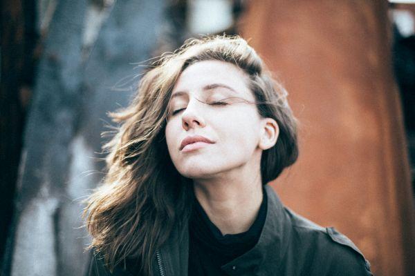 Eine junge Frau die mit geschlossenen Augen und zufriedenem Gesichtsausdruck den Wind auf ihrem Gesicht spürt
