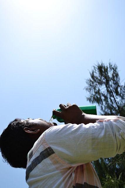 Mann trinkt Wasser aus einer Flasche und blickt gen Himmel