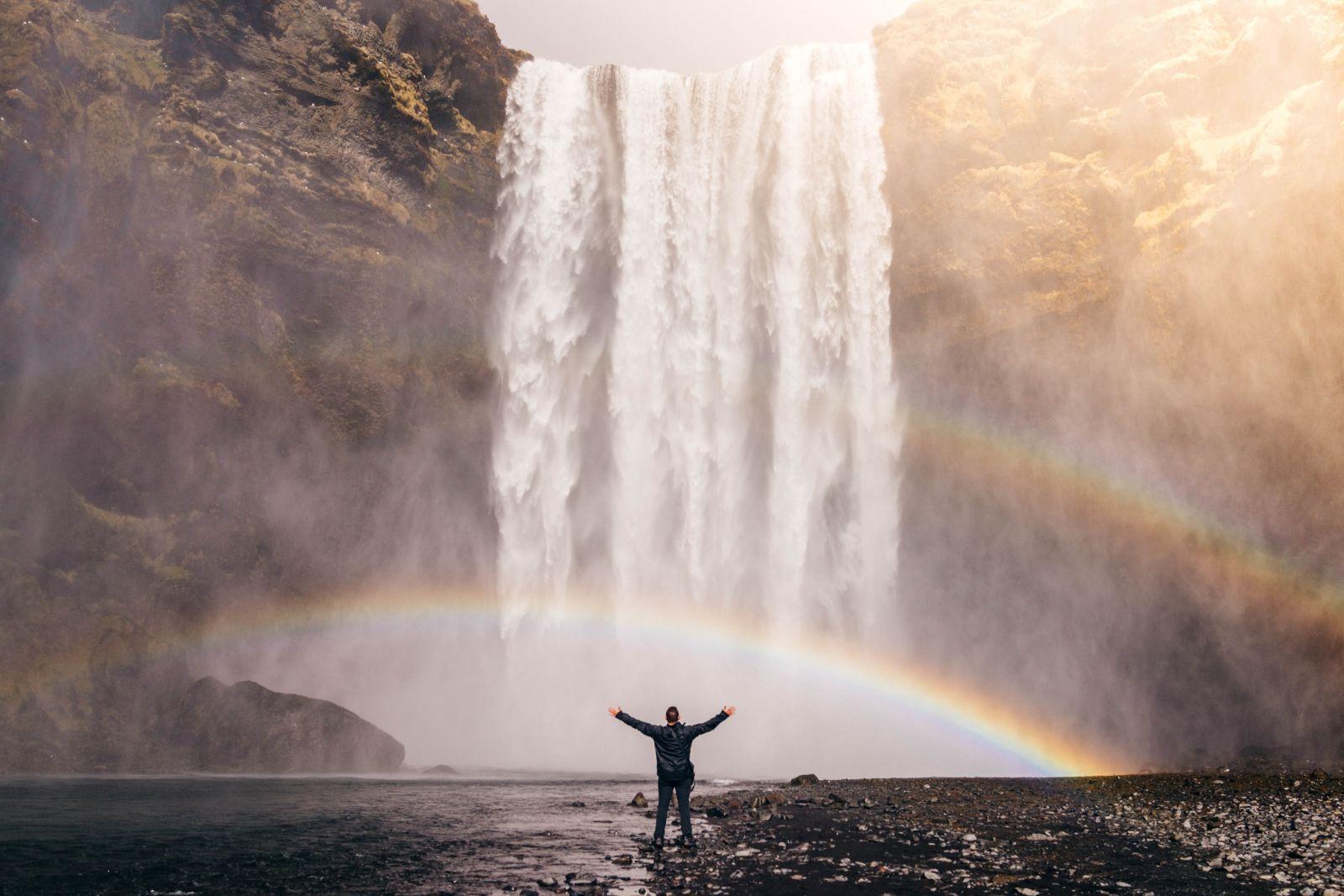 Mann steht mit offenen Armen vor einem Wasserfall in Island. Zwischen ihm und dem Wasserfall ist ein Regenbogen zu sehen.