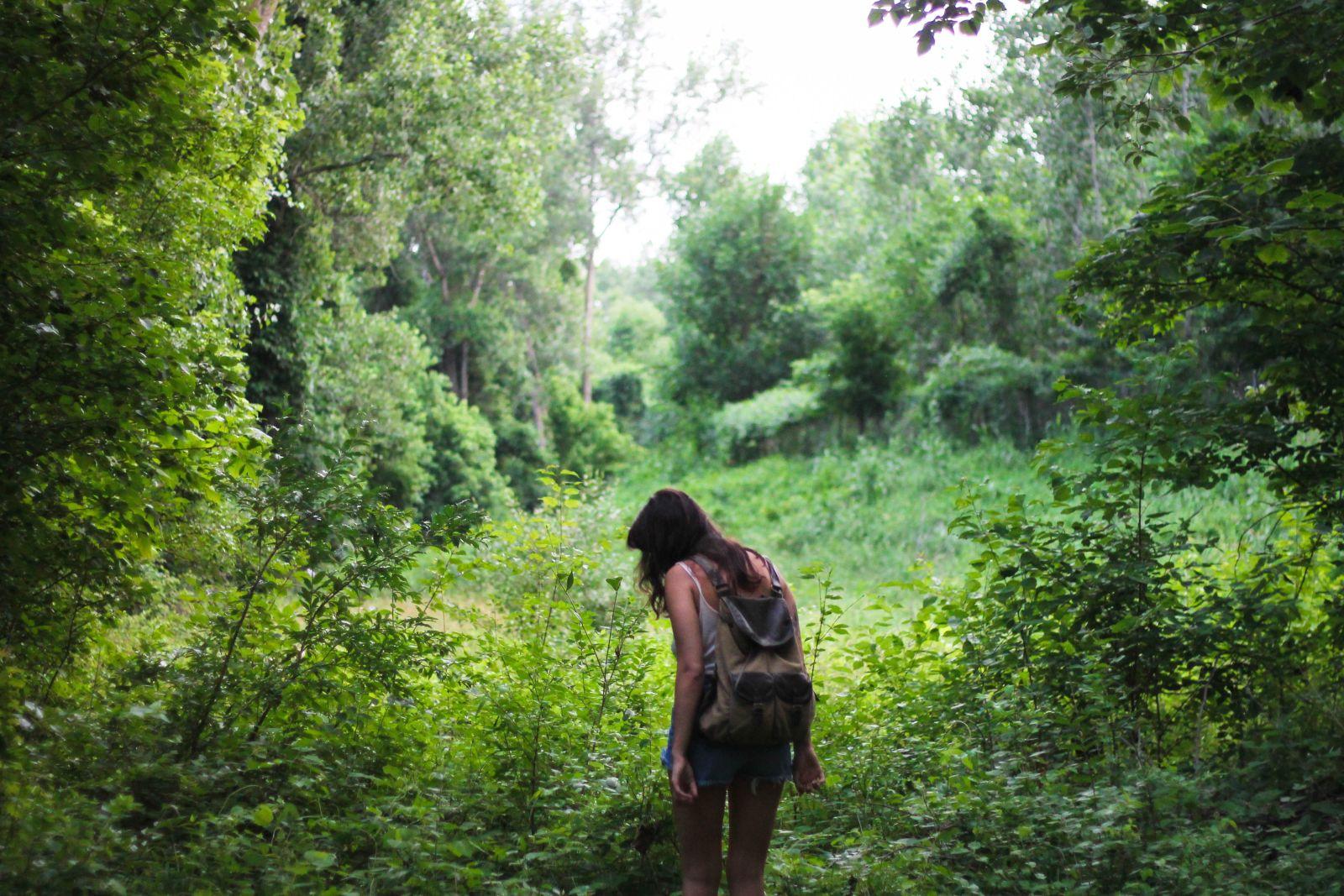 Junge Frau mitten im Wald an einer Lichtung schaut zu Boden