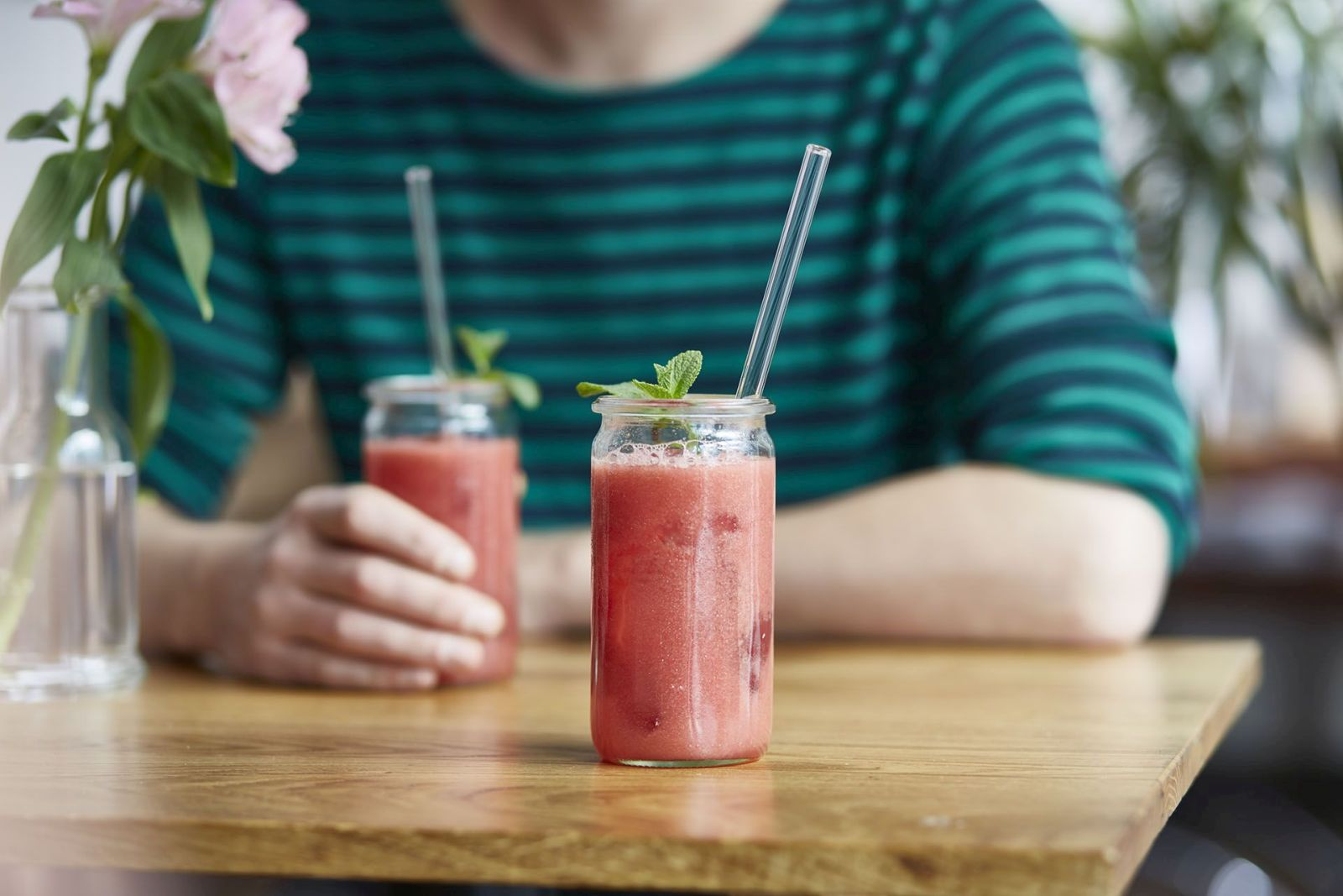 Zwei Gläser gefüllt mit rotem Obstsmoothie und darin befindet sich je einem Trinkhalm aus Glas.