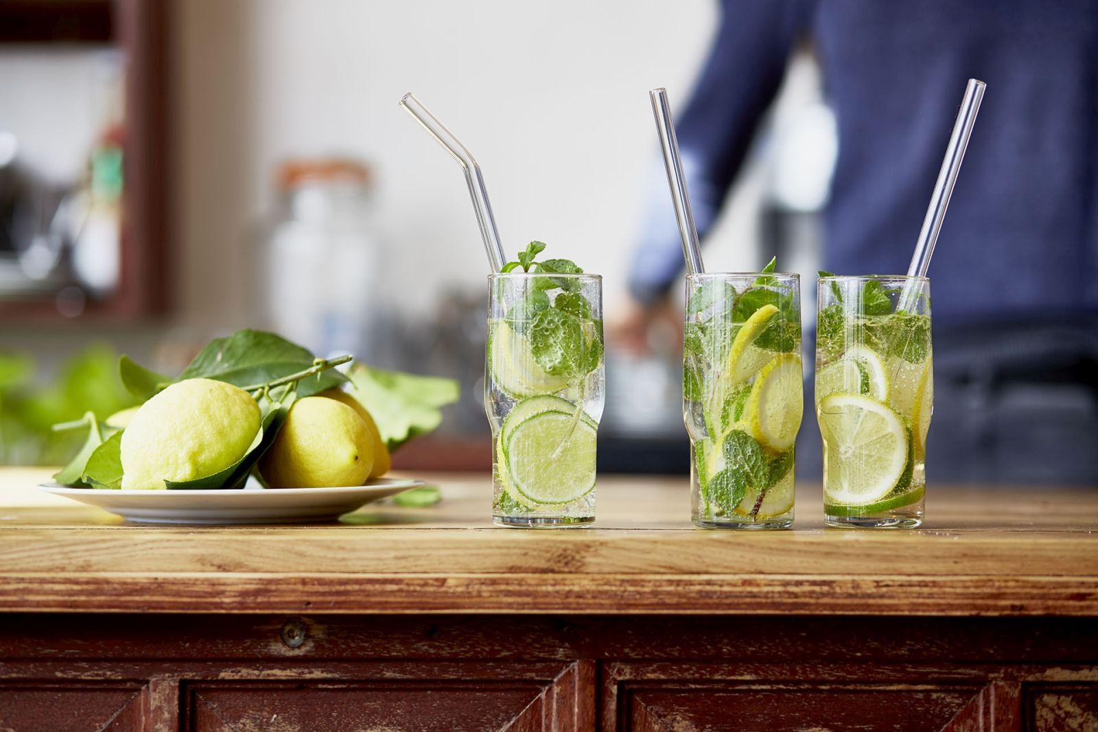 Glas-Trinkhalme in Gläsern gefüllt mit Wasser, Zitronenscheiben und Minzblättern