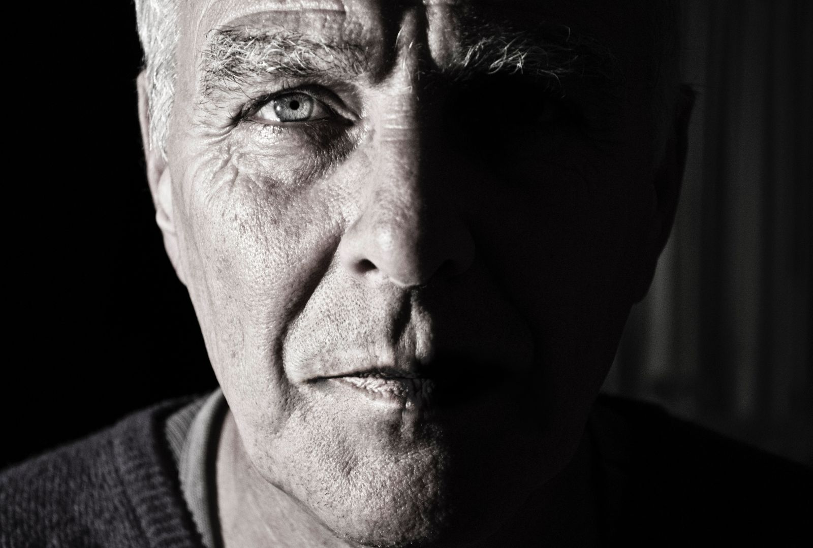 Schwarz-weißes Bild von einem Älteren Mann der direkt mit klarem Blick in die Kamera blickt