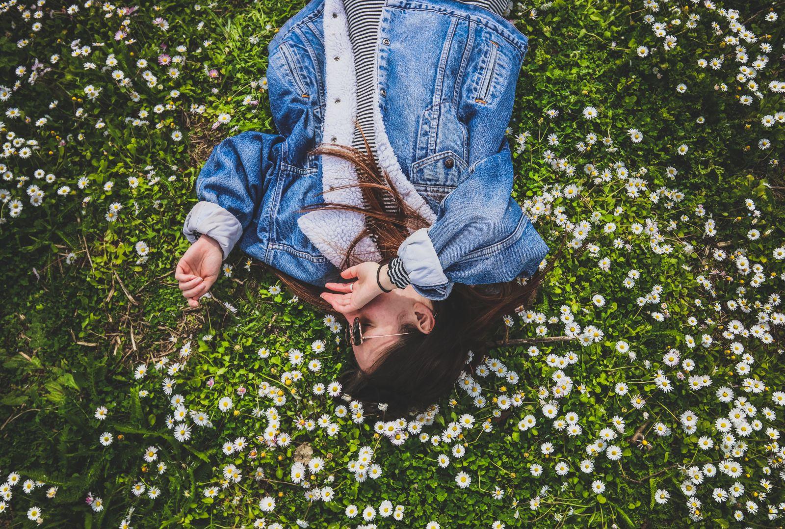 Junge Frau trägt eine gefütterte Jeansjacke und liegt im grünen Gras voller Gänseblümchen