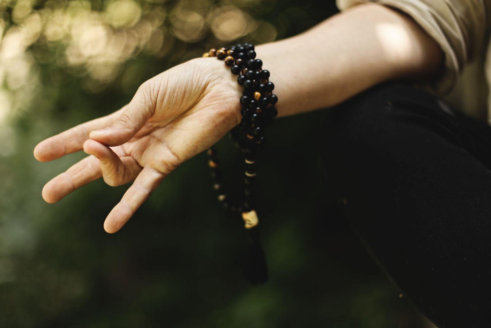 Eine Hand in Mediationsstellung. Daumen und Ringfinger berühren sich, die anderen Finger sind ausgestreckt.