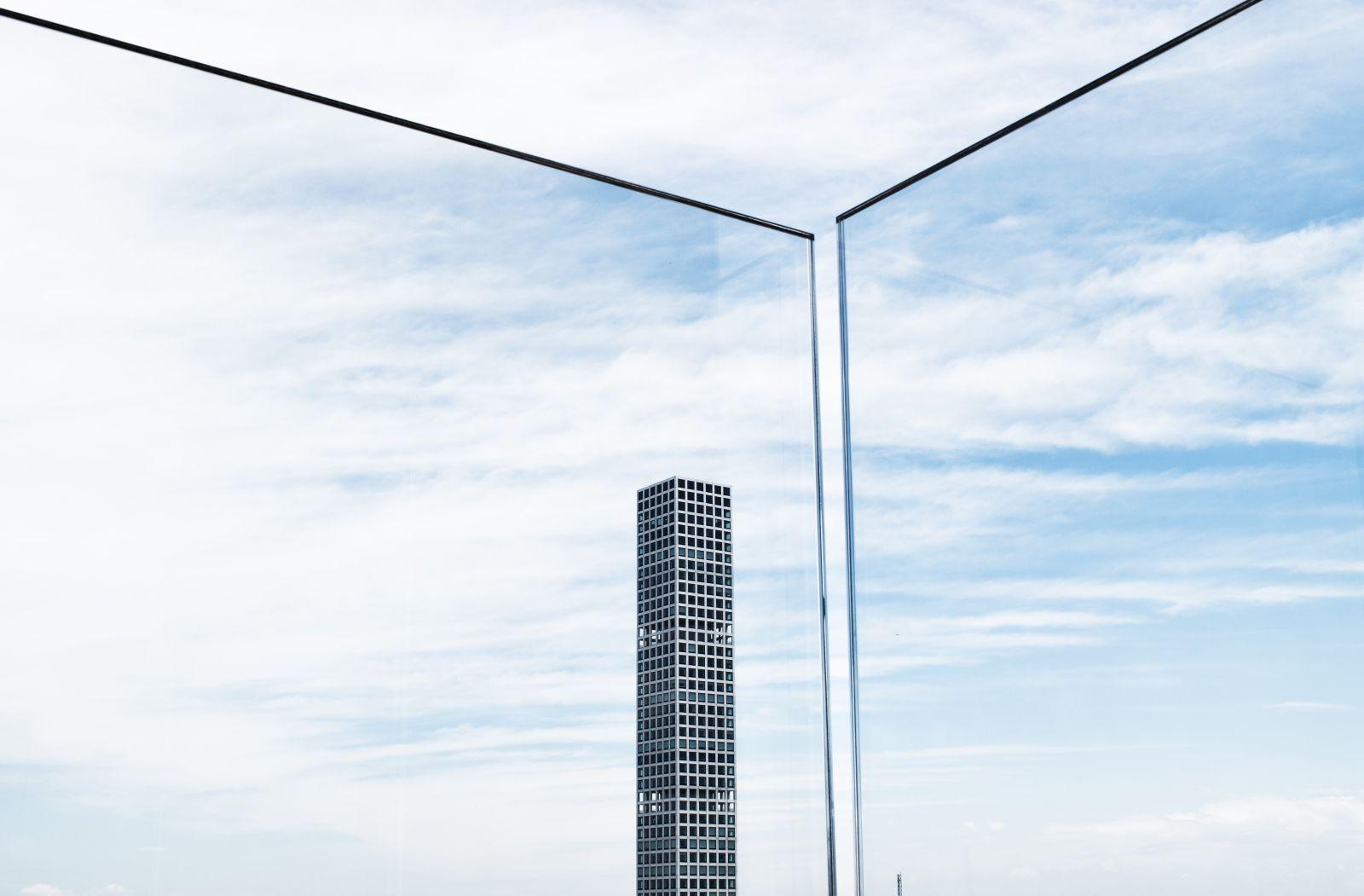 Im Vordergrund sind Glasscheiben zu sehen und im Hintergrund ein Wolkenkratzer mit lauter Fensterscheiben