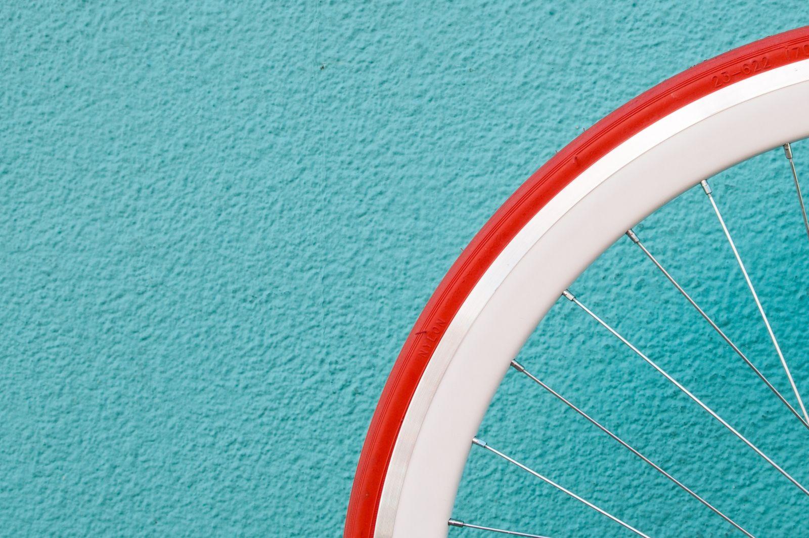 Teil eines Fahrradreifens im unteren rechten Bildrand vor einer türkisfarbenen Wand