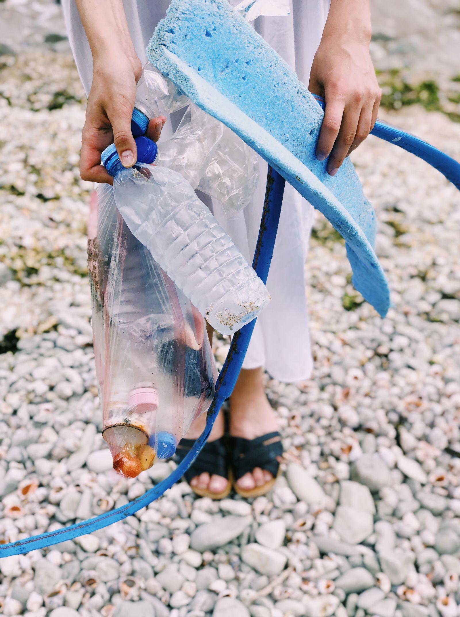 Frau sammelt Müll in der Natur und hält ihn in ihren Händen