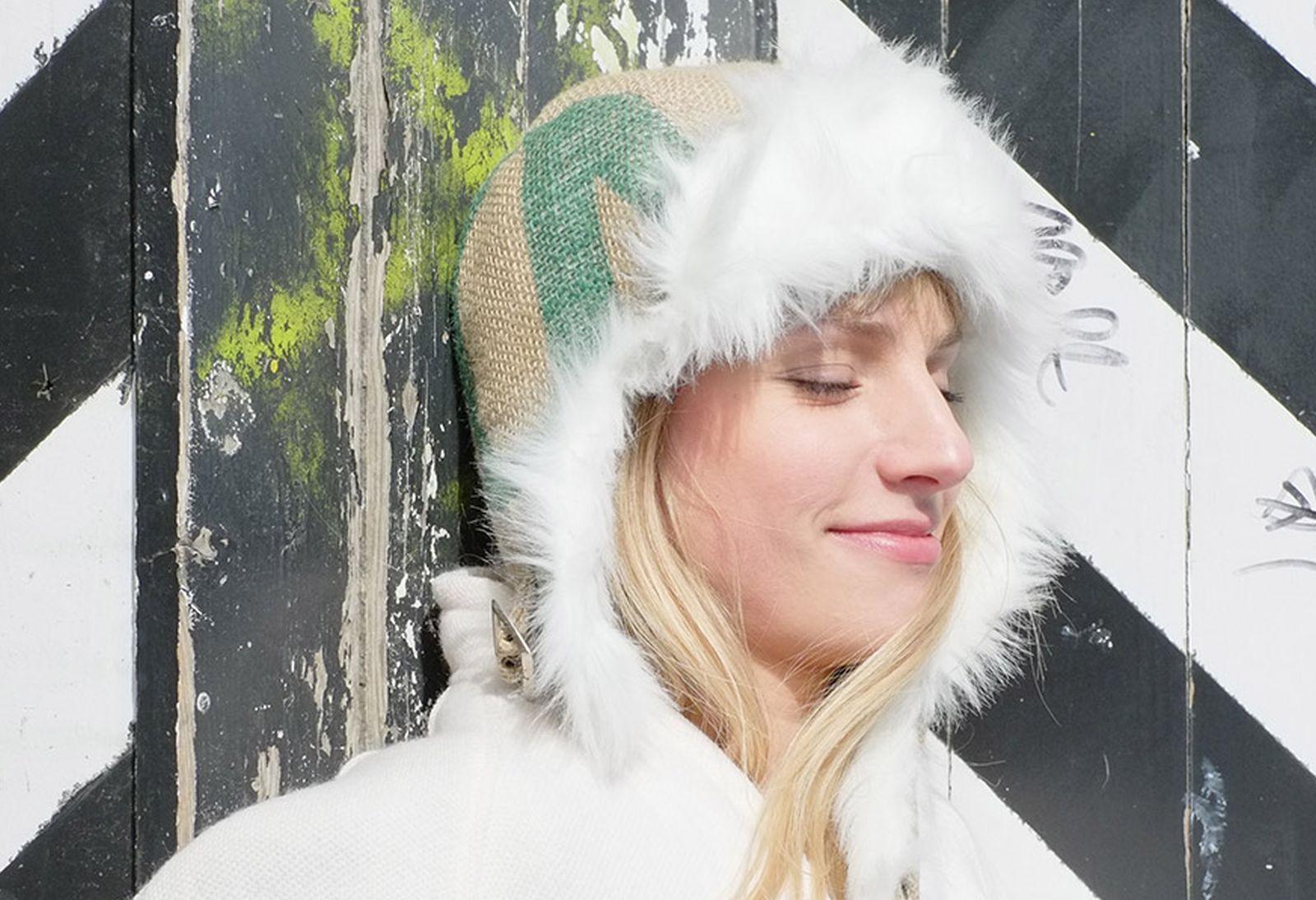 Junge, blonde Frau lehnt einer Holzwand und trägt eine vegane Wintermütze aus einem Kaffeesack