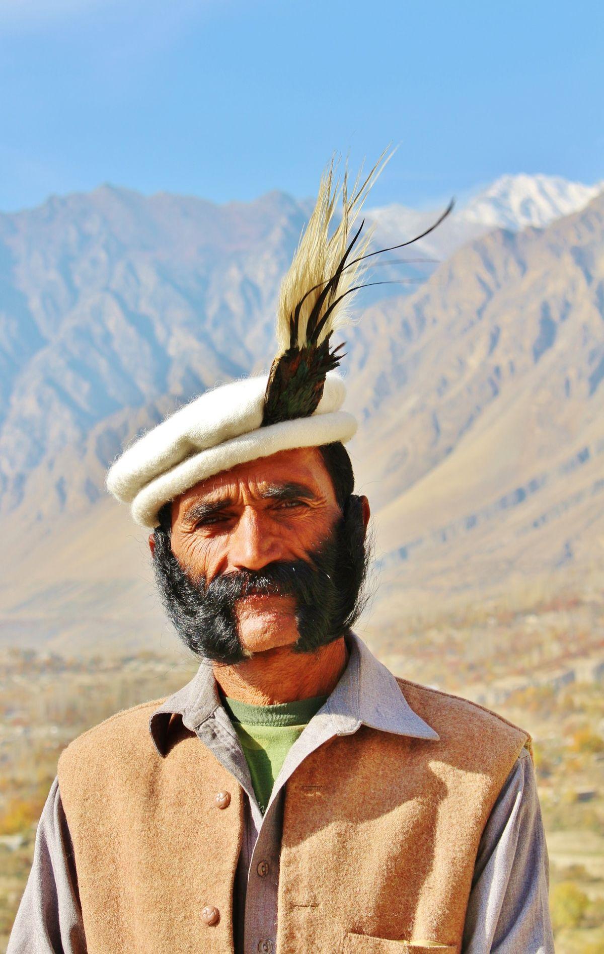 Hunzamann mit schwarzem Bart und Hut mit Federn vor einer bergigen Landschaft im Hunzatal