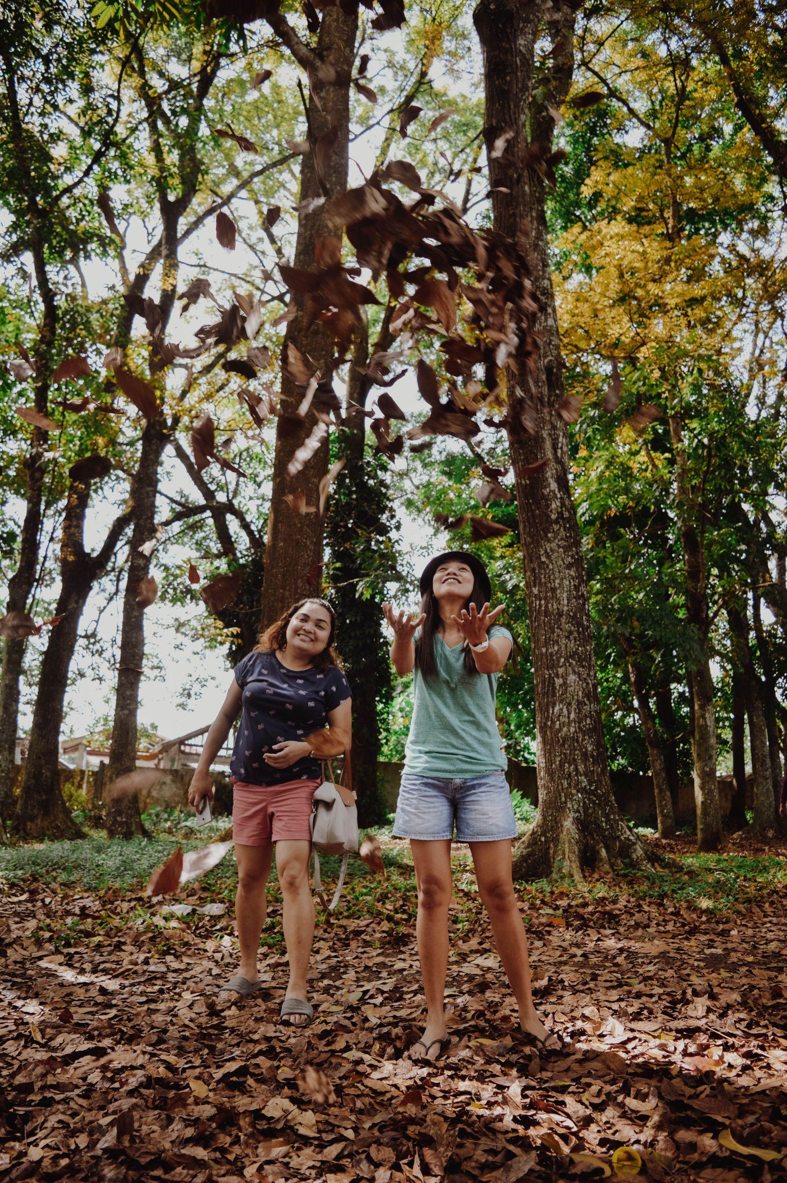 Zwei philippinische Schülerinnen freuen sich in einem Wald. Das Mädchen auf der rechten Seite wirft Laub in die Luft.