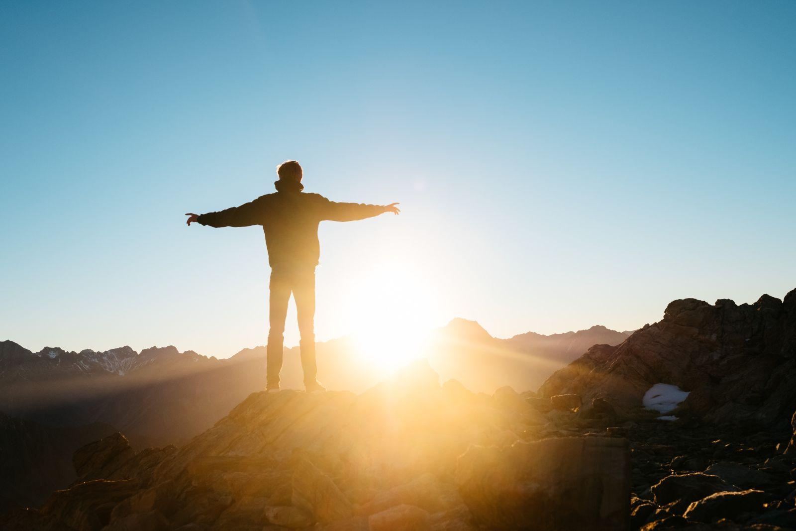 Mann von hinten auf einem Berg stehend und die Arme ausbreitend zum Sonnenaufgang schauend.