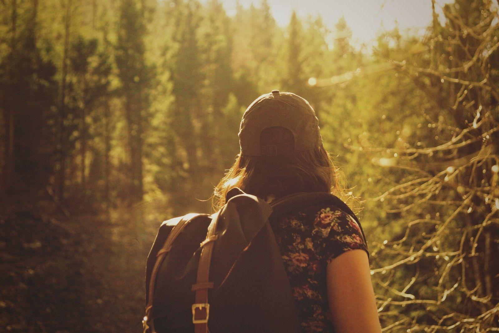 Eine Frau mit dunklen Haaren und einem Rucksack sieht man von hinten, wie sie richtung Sonne, eingehölt in goldenes Licht, in Richtung Wald blickt