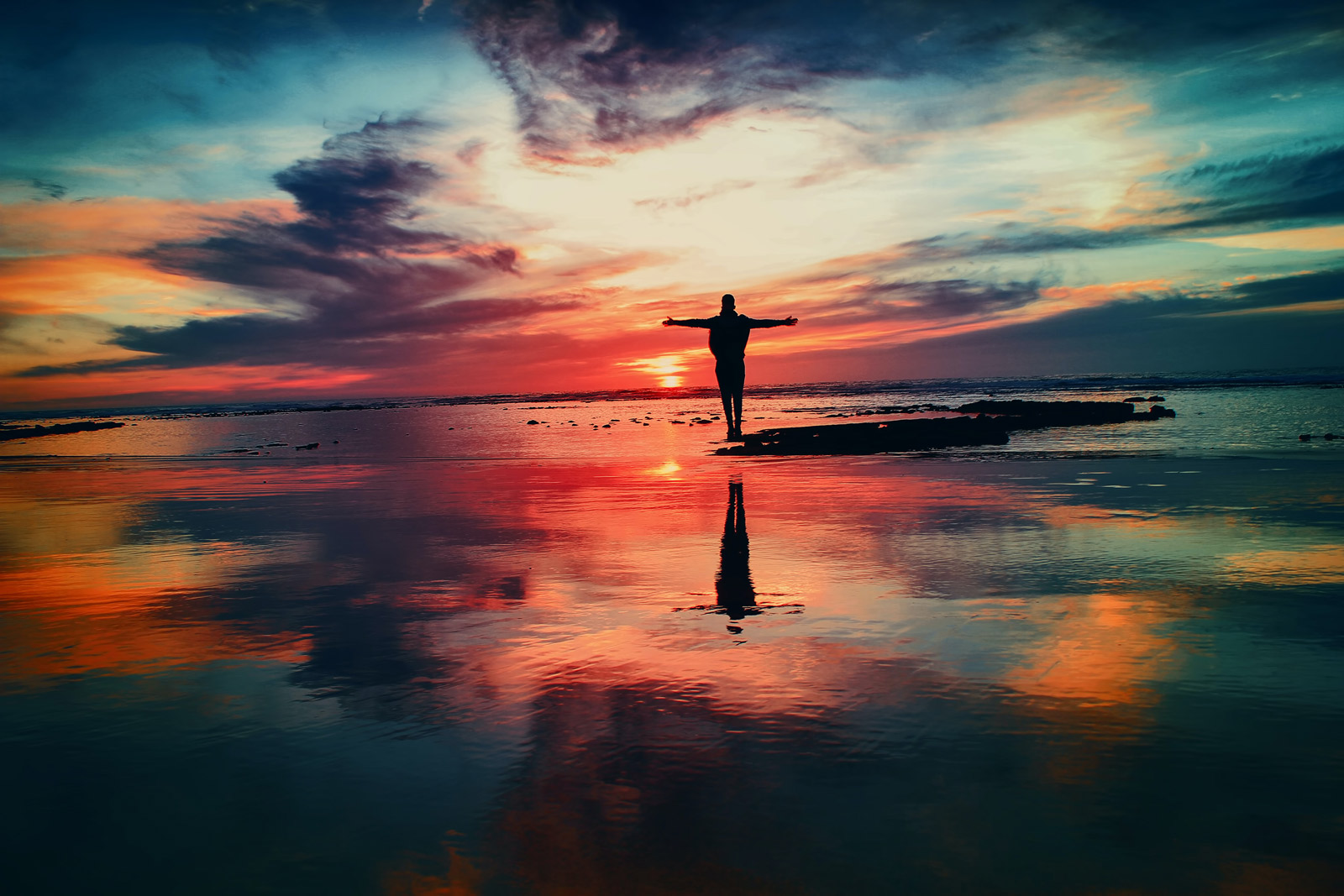 Ein Mensch steht mit offenen Armen am Wasser während die Sonne untergeht und das Firmament in bunte Farben hüllt