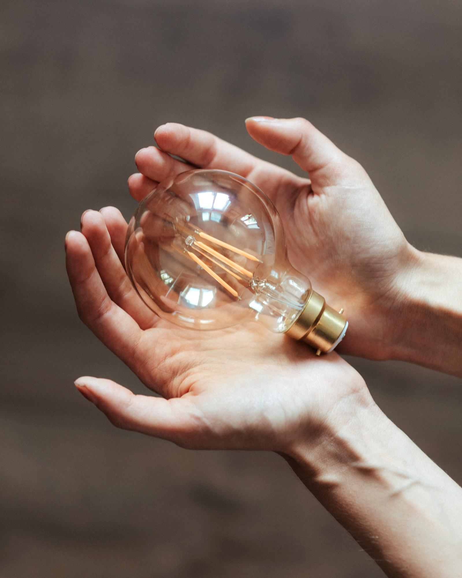 Eine Glühbirne liegt behütet in zwei aufgehaltenen Händen