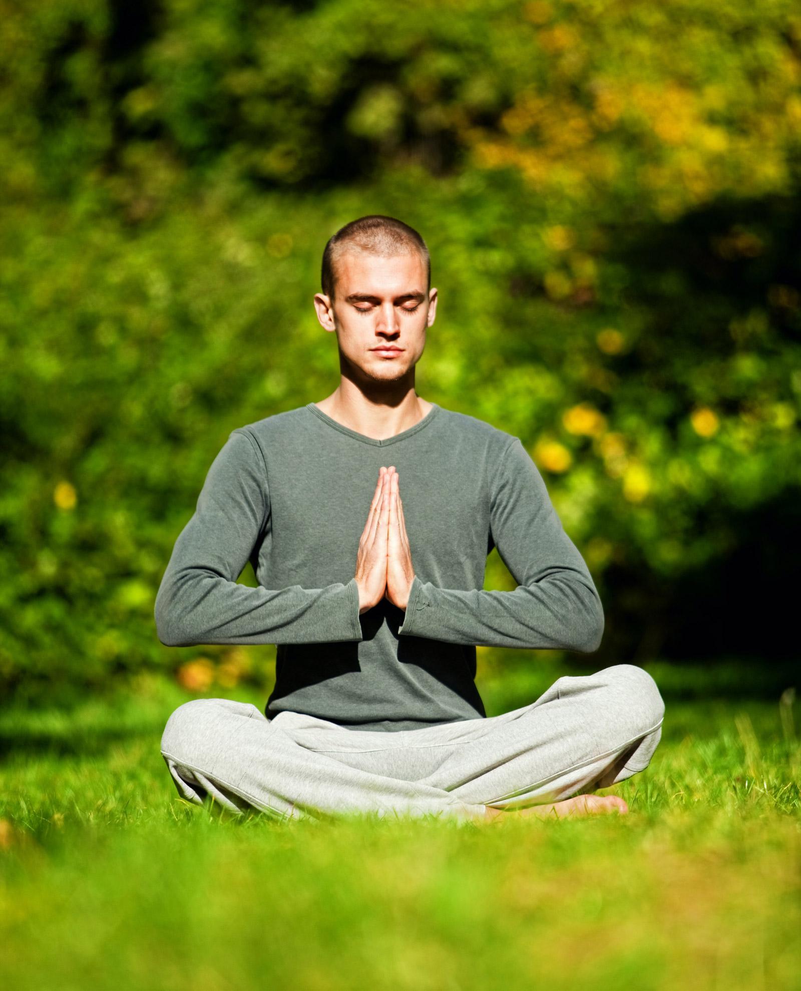 Meditierender junger Mann sitzt im Schneidersitz auf einer grünen Wiese. Seine Hände sind in Gebetshaltung und vor dem Herzchakra platziert.